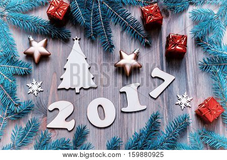 Happy New Year 2017 background with 2017 figures Christmas toys fir branches- New Year 2017 still life.Concept of Happy New Year 2017 holiday with New Year objects in vintage tones.Flat lay top view