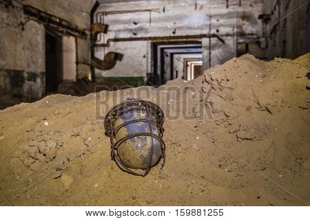 Old broken rusty soviet lantern in the sand on background of abandoned soviet bunker