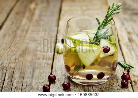 Apple Cranberry Rosemary sangria on wood background