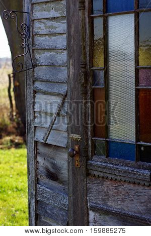 antique weathered wood outhouse door with stained glass window and intricate wood work
