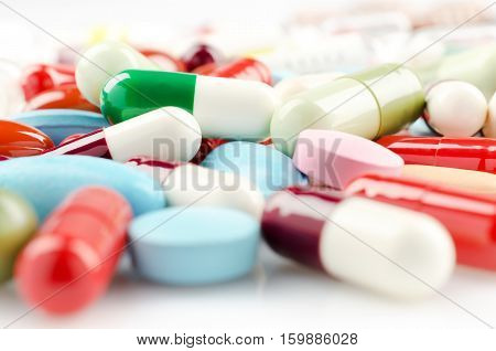 Pharmacy theme. Multicolored Isolated Pills and Capsules on the White Surface. Closeup