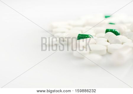 Medical theme. Bright white and green pills on the white surface. Closeup