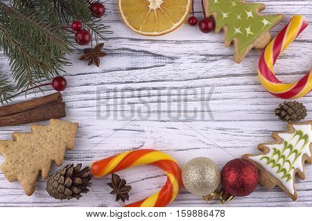 Christmas Xmas New Year holiday Background with dried oranges cookies star anise cinnamon cones natural fir branches cande cane on white wood