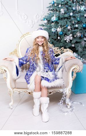 Little beautiful girl sit on the Santa's chair in a Christmas costume. Frozen girl. Winter season. Merry Christmas.