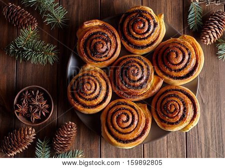Cinnamon rolls buns christmas baking on a wooden breakfast table. Top view. Festive decoration with pine cones and Christmas tree