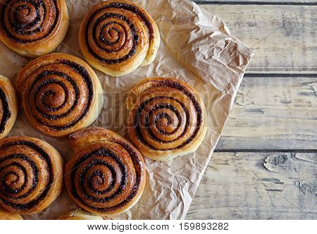 Freshly baked cinnamon rolls buns with cocoa and spices on wooden table and parchment paper. Close-up. Top view. Kanelbulle swedish pastry dessert. Christmas baking pastry.