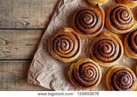 Cinnamon rolls buns christmas baking on a wooden breakfast table and parchment paper. Top view. Festive decoration with pine cones and Christmas tree