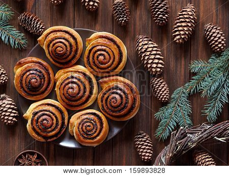 Sweet Homemade christmas baking. Cinnamon rolls buns with cocoa filling. Kanelbulle swedish dessert. Festive decoration with pine cones and Christmas tree