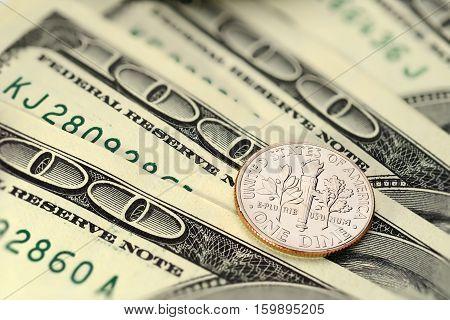 Dime US cent coin on hundred dollar bills. Macro shot