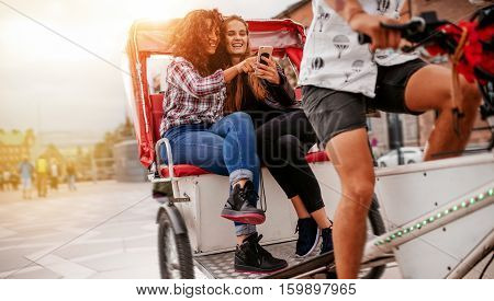 Teenage girls sitting on tricycle using mobile phone. Female friends enjoying tricycle ride on road and using smart phone.
