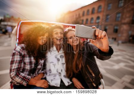 Three young friends taking selfie on tricycle ride. Group of people riding on tricycle bike and taking self portrait. Focus on mobile phone in female hand.
