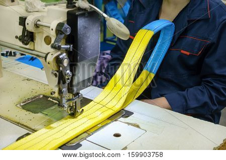 Industrial sewing machine sews a webbing sling. Manufacture of textile slings and tie straps.