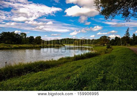Bright blue sky with white clouds overlooking grass covered riverbank