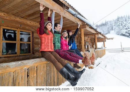 People Group Sitting On Terrace Wooden Country House Winter Snow Resort Cottage Friends Communication Vacation