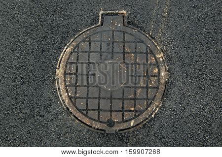 Manhole cover in a fresh asphalthole Cover