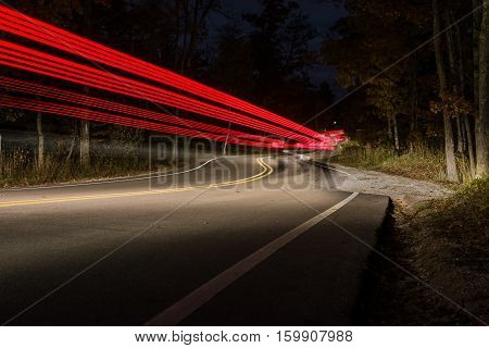 Curved road at night with cars driving up and down causing light trails.