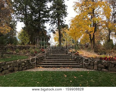 Pioneer Park in the city of Bend in Central Oregon on a fall morning with fallen leaves a rock wall and stairs.