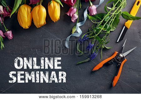 Text ONLINE SEMINAR with flowers on dark background. Florist and floral design tutorial concept.
