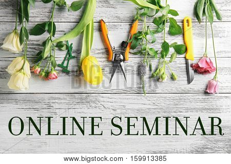 Text ONLINE SEMINAR with flowers on white wooden background. Florist and floral design tutorial concept.