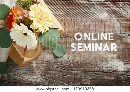 Gift box decorated with flowers and text ONLINE SEMINAR on wooden background. Florist and floral design tutorial concept.
