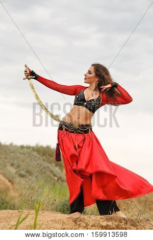 Oriental Beauty dance with a sword. Tribal style. Lovely girl in costume dancing outdoors. Nomads.