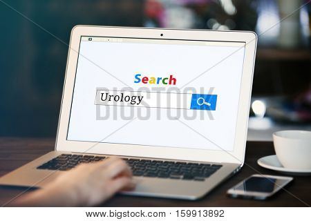 Woman searching information on internet, closeup. Word UROLOGY at search engine. Health care concept.