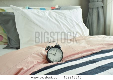 Black Alarm Clock On Bed With Colorfull Bedding