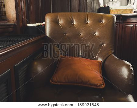 Old vintage dark brown sofa chair in cafe.