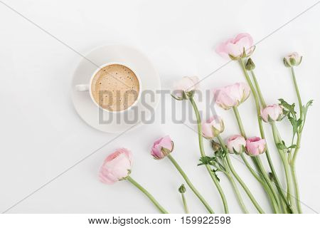 Beautiful spring Ranunculus flowers and cup of coffee on white desk from above. Greeting card. Breakfast. Pastel color. Clean space for text. Flat lay style.