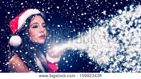 Portrait of a beautiful Christmas girl blowing magic snow. Wide image