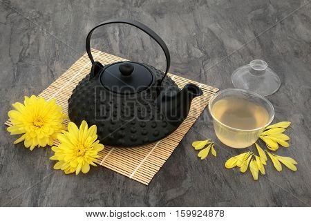Chrysanthemum flower tea with flowers, oriental teapot and glass cup with lid on bamboo mat. Also used  in traditional chinese herbal medicine.
