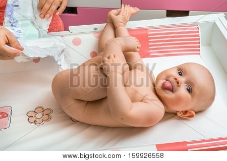 Mother Changing Diaper To Her Little Baby Girl