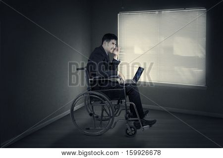 Portrait of a disabled male entrepreneur expressing anger with laptop and sitting on a wheelchair near the window