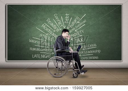 Image of disabled businessman sitting in a wheelchair while thinking his problem with laptop and chalkboard in the office