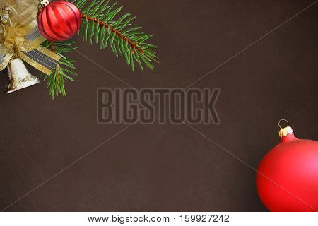 Christmas fir branch red wavy dull ball and bell on a dark background