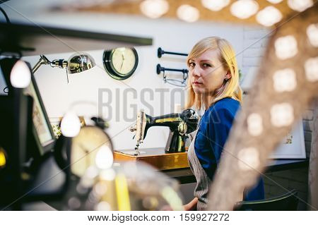 Seamstress Work On The Sewing Machine. Young Blonde Woman Working On A Mechanical Sewing Machine At