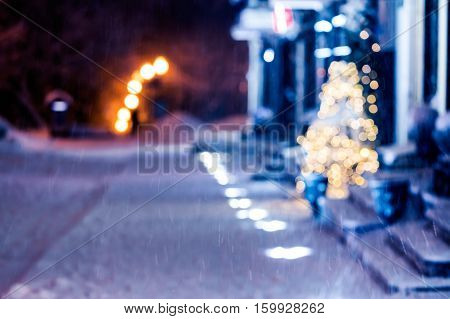 blurred glowing christmas lights and street in snow create festive atmosphere