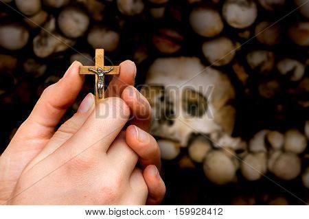 Female Hands With Cross On Skulls And Bones Background