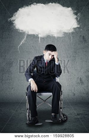 Portrait of disabled Arabian businessman sitting on a wheelchair and expressing stressful with a storm cloud above his head