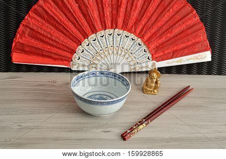 Chines bowl chopsticks a hand fan and a laughing Buddha