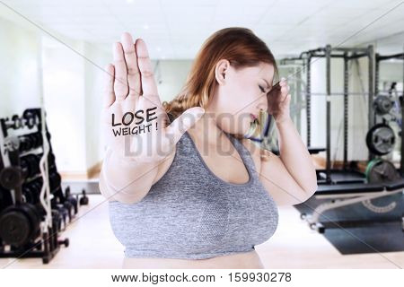 Portrait of obese woman showing lose weight text on her hand while holding her head at the gym