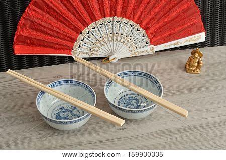 Chines bowls chopsticks a hand fan and a laughing Buddha