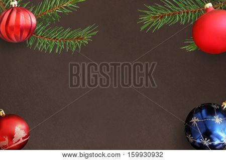 red wavy dull and blue ball on dark background with Christmas fir branch