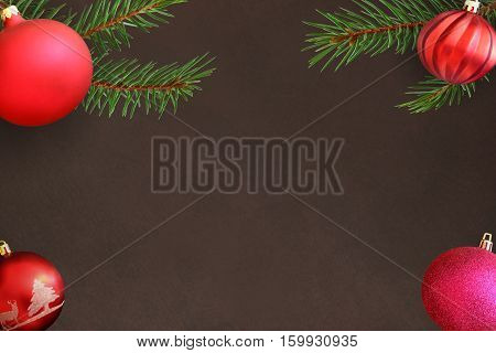 Christmas tree branch with pink and red wavy dull ball on a dark background. Top view.