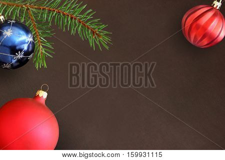 Dark background with Christmas fir branch blue and red wavy dull ball