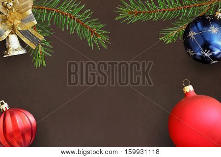Christmas branches of spruce blue and red wavy dull balloon and decorative bell on dark background