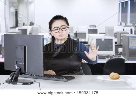 Young businesswoman refuse boiled potato while sitting in front of her computer