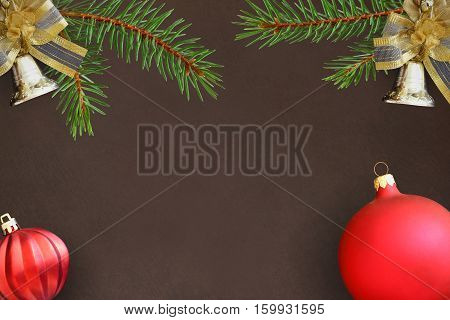 dark background with branches of spruce Christmas decorative bells and red wavy dull ball