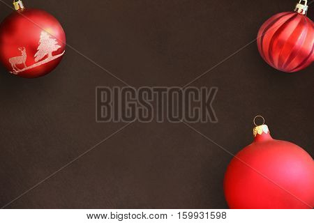 Christmas red and wavy dull balls on dark wooden table. Top view.