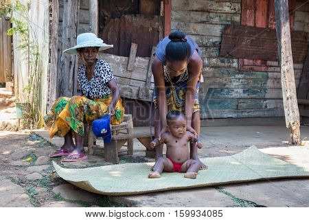 Malagasy Woman With Baby Resting In Shadow, Madagascar